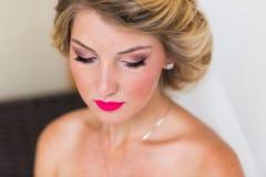 愉快的少妇和与花的新娘面纱画象白色婚礼礼服的 免版税图库摄影