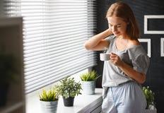 愉快的少妇喝咖啡在窗口在早晨 免版税图库摄影