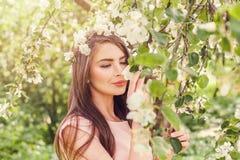 愉快的少妇嗅到的花在开花春天开花 库存图片