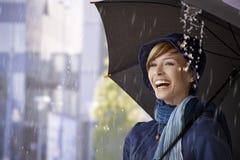 愉快的少妇在伞下在雨中 免版税库存图片
