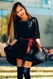 愉快的少妇在公园在晴朗的秋天天,微笑 黑减速火箭的礼服秋天时尚样式的快乐的美丽的女孩 库存图片