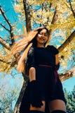 愉快的少妇在公园在晴朗的秋天天,微笑 黑减速火箭的礼服秋天时尚样式的快乐的美丽的女孩 图库摄影