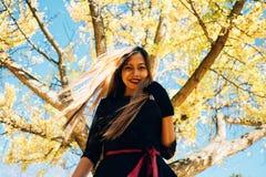 愉快的少妇在公园在晴朗的秋天天,微笑 黑减速火箭的礼服秋天时尚样式的快乐的美丽的女孩 免版税库存照片