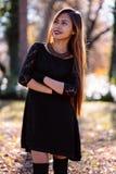 愉快的少妇在公园在晴朗的秋天天,微笑 黑减速火箭的礼服秋天时尚样式的快乐的美丽的女孩 免版税库存图片