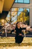 愉快的少妇在公园在晴朗的秋天天,笑,使用离开 黑减速火箭的礼服秋天fashi的快乐的美丽的女孩 库存照片