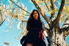 愉快的少妇在公园在晴朗的秋天天,笑,使用离开 黑减速火箭的礼服秋天fashi的快乐的美丽的女孩 免版税库存图片
