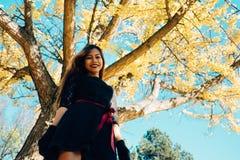 愉快的少妇在公园在晴朗的秋天天,笑,使用离开 黑减速火箭的礼服秋天fashi的快乐的美丽的女孩 库存图片
