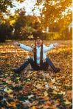 愉快的少妇在公园在晴朗的秋天天,笑,使用离开 白色毛线衣的快乐的美丽的女孩在秋天se期间 免版税库存照片