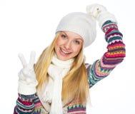 愉快的少妇在冬天给显示胜利姿态穿衣 免版税库存照片
