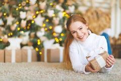 愉快的少妇在圣诞树的早晨与礼物 免版税库存照片
