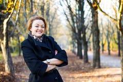 愉快的少妇在秋天公园 免版税库存图片