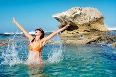 愉快的少妇在水中跳 免版税库存照片