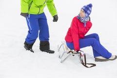 愉快的少妇坐雪撬,当看雪的时人 免版税图库摄影