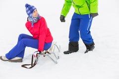 愉快的少妇坐雪撬,当看雪的时人 库存图片