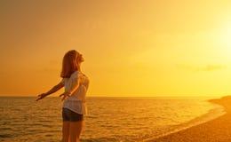 愉快的少妇对天空和海张开她的胳膊在日落 免版税库存图片