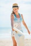 愉快的少妇帽子的和有有的袋子的在海滩的乐趣时间 免版税库存照片