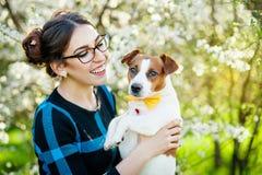 愉快的少妇拥抱和获得与她的杰克罗素狗的乐趣在开花的庭院里 库存图片