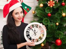 愉快的少妇拿着一个时钟并且微笑着,当在家时庆祝圣诞节 免版税库存照片