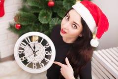 愉快的少妇拿着一个时钟并且微笑着,当celebrati时 库存图片