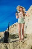 愉快的少妇旅客伸手可及的距离沙丘上面  免版税库存图片