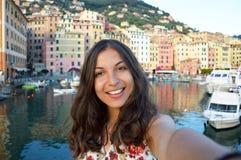 愉快的少妇晒黑了拍在一个典型的意大利风景的selfie照片与港口和五颜六色的房子意大利假日 免版税库存图片