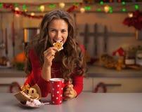 愉快的少妇有吃圣诞节曲奇饼在厨房 免版税库存图片