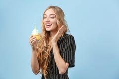 愉快的少妇用生日杯形蛋糕 免版税库存图片