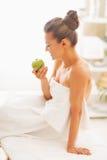愉快的少妇用苹果坐按摩桌 库存图片