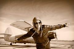 愉快的少妇用飞行在airporte的被举的手, 免版税库存照片
