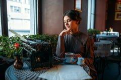 愉快的少妇由在咖啡馆的桌坐 免版税库存照片