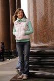 愉快的少妇站立在老和大柱子之间 免版税图库摄影