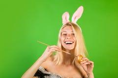 愉快的少妇绘画鸡蛋 愉快的人员 微笑复活节 美丽白肤金发肉欲 惊人的美丽的少女  免版税图库摄影