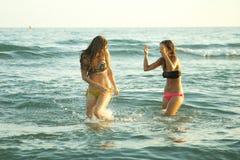 愉快的少妇获得乐趣在海在夏天 免版税库存照片