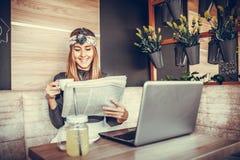 愉快的少妇读书报纸和饮用的咖啡在coff 免版税库存图片