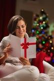 愉快的少妇读取圣诞节明信片 免版税库存图片