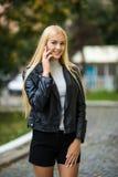 愉快的少妇谈话在手机在城市街道生活方式画象 有手机的微笑的女孩听见好消息的 相当 库存图片
