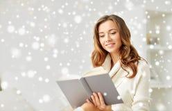 愉快的少妇阅读书在家 免版税库存图片