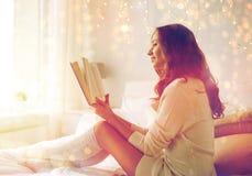 愉快的少妇阅读书在床上在家 图库摄影