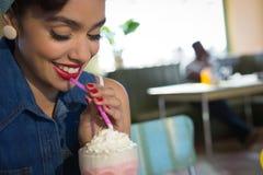 愉快的少妇食用奶昔在餐馆 免版税库存图片