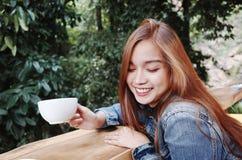 愉快的少妇饮用的咖啡户外和使用智能手机 免版税图库摄影