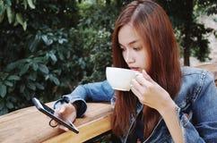 愉快的少妇饮用的咖啡户外和使用智能手机 库存图片