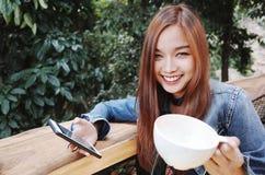 愉快的少妇饮用的咖啡户外和使用智能手机 图库摄影