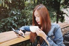 愉快的少妇饮用的咖啡户外和使用智能手机 免版税库存照片