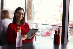 愉快的少妇饮用的柠檬水/冰了茶和使用片剂计算机在咖啡店 库存照片