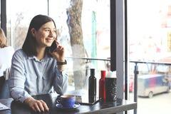 愉快的少妇饮用的热奶咖啡,拿铁, macchiato,茶,使用片剂计算机和谈话在咖啡店/ba的电话 免版税图库摄影