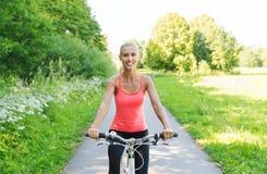 愉快的少妇骑马自行车户外 免版税图库摄影