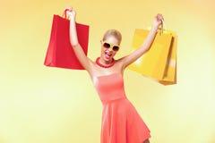 愉快的少妇购物在黑星期五假日 有许多颜色袋子和礼物的女孩 免版税库存图片