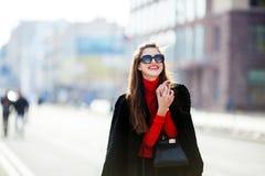 愉快的少妇画象的室外生活方式关闭时髦的偶然成套装备画象的在街道上 她微笑并且看 免版税库存图片