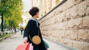 愉快的少妇shopaholic跳舞的慢动作在街道的有转动和转动看的明亮的购物袋的 影视素材
