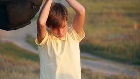 愉快的少年男小学生在背包附近转动 学生在时代结束时高兴 影视素材